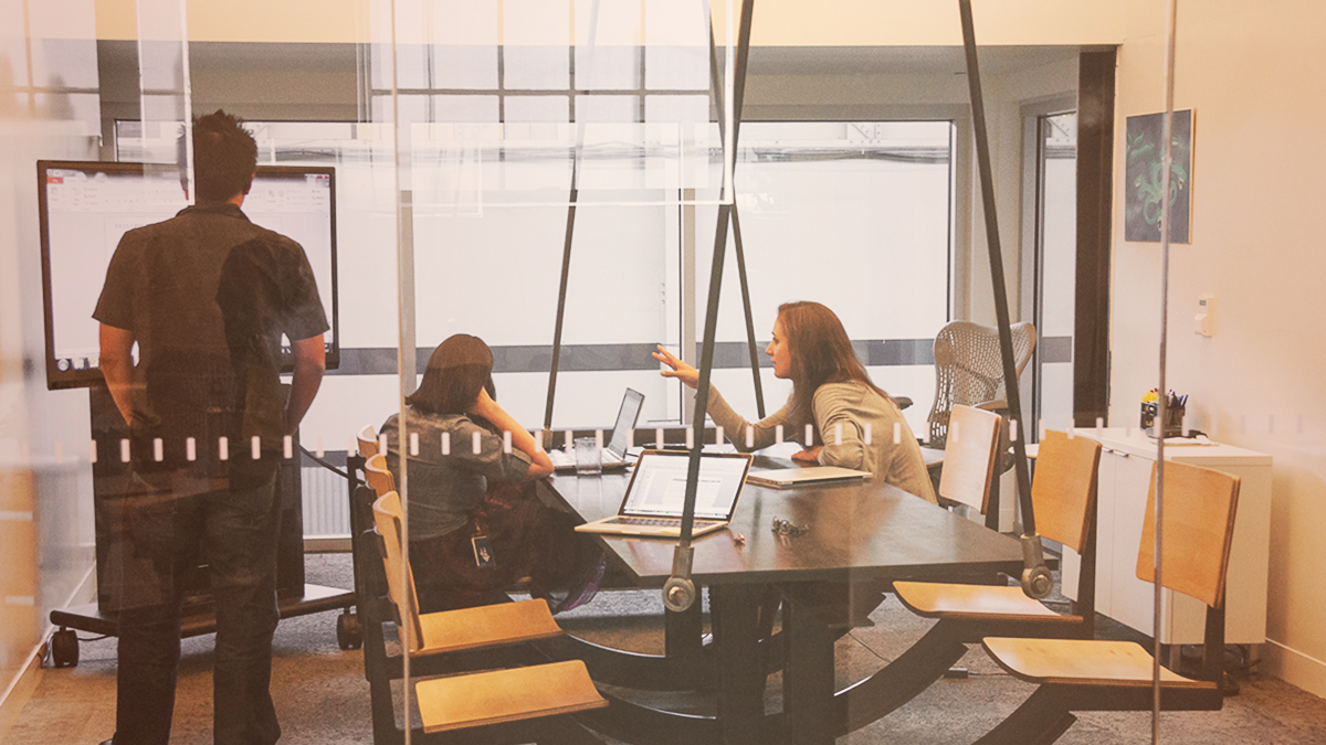 Three People Discussing A Project At Table In Meeting Room Image Used As