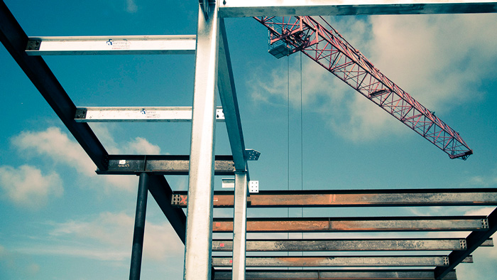 Photo of steel beams and girders with construction crane in background, used as supporting image for a blog post on the importance of BIM cloud technology for structural engineers and detailers