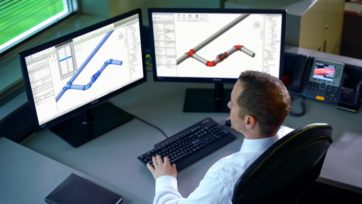 Photo of an engineer looking at two screens with 3D models of pipe fittings, courtesy of Victaulic. The images accompanies a blog post on the benefits of cloud worksharing and collaboration in BIM 360 Design for teams using Revit.