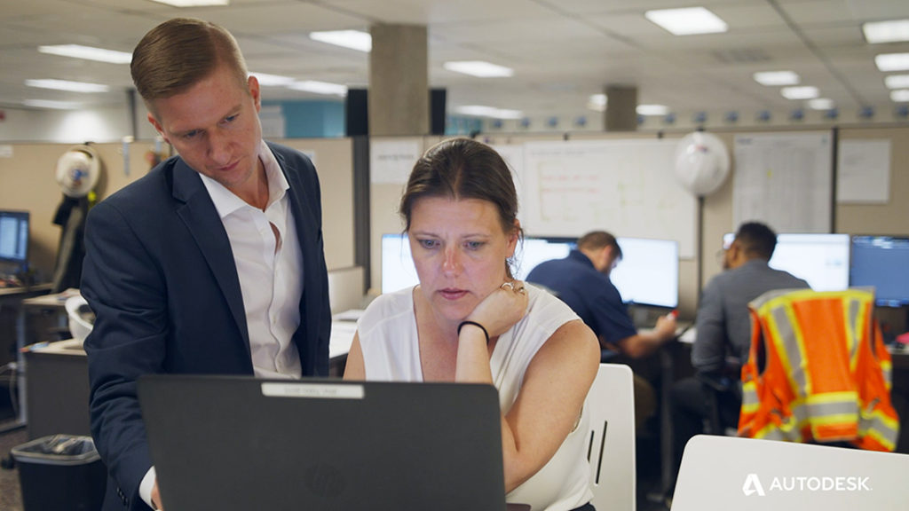Image of Jennifer Berg (right, seated) and Tim Totin (left, standing) looking at the same laptop screen. Used as supporting image for blog post on Glumac's approach to sustainable design collaboration.