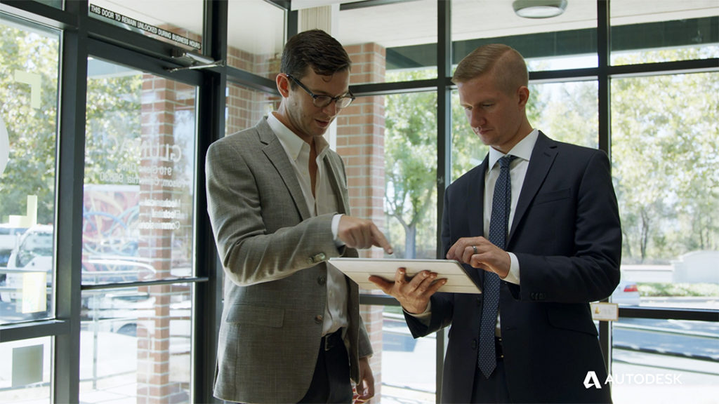 Nick Gallucci, dressed in a suit on the left, points at the screen of an iPad that Tim Totin, also dressed in a suit, is holding on the right. Supporting image used on a blog post about Glumac's sustainable design collaboration processes in project delivery.