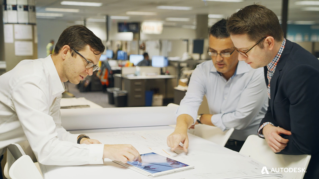 Nick Gallucci, Ron Milson, and Alex Baumgardner (left to right) point at an iPad on top of a stack of construction drawings.
